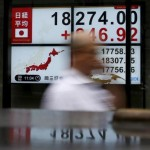 A pedestrian walks past electronic boards showing the Japan's Nikkei average outside a brokerage in Tokyo, Japan, September 9, 2015.  REUTERS/Yuya Shino