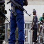 Residents look on as police and soldiers guard a voting station in Burundi's capital Bujumbura during the country's presidential elections, July 21, 2015.   REUTERS/Mike Hutchings