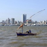 Traditional fishing boats sail as Mozambique's tuna fleet sits in dock beneath Maputo's skyline, in this picture taken August 15, 2015. REUTERS/Grant Lee Neuenburg
