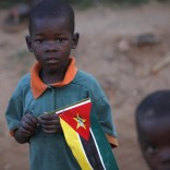 "A child clasps a Mozambique flag in a suburb on the outskirt of the capital Maputo in this file picture taken November 2009. At Bobole, a bustling refreshment stop on Mozambique's north-south highway, brightly-painted kiosks lined with bottles offer drinks to thirsty travellers while hawkers sell bananas, paw-paws and carrots in a typical African roadside scene. But memories remain fresh of when Bobole lay in the ""death corridor"" of a civil war that cost nearly one million Mozambicans their lives until it ended two decades ago. In 2013 a series of hit-and-run raids by opposition Renamo gunmen about 600 km (375 miles) further north has rekindled fears of a return to all-out conflict in what has become one of Africa's economic growth stars. To match Insight MOZAMBIQUE-POLITICS/  REUTERS/Mike Hutchings/Files (MOZAMBIQUE - Tags: SOCIETY POLITICS BUSINESS CIVIL UNREST)"