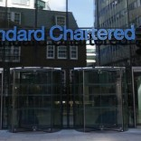 A man walks past the head office of Standard Chartered bank in the City of London February 27, 2015. I REUTERS/Eddie Keogh