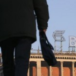 A pedestrian walks on a street, with the logo of VTB Bank displayed on the roof of a building, in Moscow, November 20, 2014.  REUTERS/Maxim Zmeyev