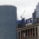 "The logo of VTB Bank is displayed on the roof of a building, with towers of the Moscow International Business Center, also known as ""Moskva-City"", seen in the background, in Moscow March 18, 2013. REUTERS/Sergei Karpukhin"