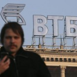 A man walks in a street, with the logo of VTB Bank displayed on the roof of a building, in Moscow, November 20, 2014.   REUTERS/Maxim Zmeyev