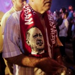 A supporter wears a scarf depicting Turkish President Tayyip Erdogan during a pro-government demonstration at Taksim square in Istanbul, Turkey, July 19, 2016. Picture taken July 19, 2016.  REUTERS/Alkis Konstantinidis