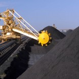 A bucketwheel reclaimer rides on rails between huge coal stockpiles at the Port Waratah coal loading facility in Newcastle, Australia Tuesday, June 1, 2004. Australian exports rose to the second highest on record in October, narrowing the trade deficit more than expected, as miners including Portman Ltd. and BHP Billiton earned more from commodity shipments to China. Photographer: Gillianne Tedder/Bloomberg News
