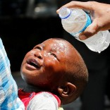 A woman pours water over a child affected by teargas after clashes between police and street vendors in central Harare, Zimbabwe, September 27, 2016. REUTERS/Philimon Bulawayo