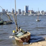 A fisherman cleans his boat beneath Maputo's skyline, in this picture taken August 15, 2015.  REUTERS/Grant Lee Neuenburg
