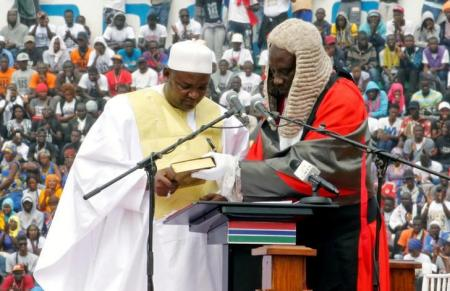 Gambia's new President Adama Barrow holds the Koran during the swearing-in ceremony at the Independence Stadium, in Bakau, Gambia February 18, 2017. REUTERS/Thierry Gouegnon