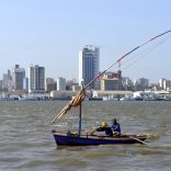 """Traditional fishing boats sail as Mozambique's tuna fleet sits in dock beneath Maputo's skyline, in this picture taken August 15, 2015. Mozambique, one of the world's poorest countries, discovered the reserves off its coast between 2010-2013, offering an opportunity to transform the former Portuguese colony which was ravaged by a 16-year civil war that ended in 1992. Recent signs of reckless government spending and an uptick in political violence have raised concerns that Mozambique could be the latest African country to suffer the resource """"curse,"""" in which an influx of petro-dollars suffocates the rest of the economy, encourages corruption and stirs unrest.  Picture taken August 15, 2015.  REUTERS/Grant Lee Neuenburg - RTX1TA2Z"""