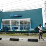 A man stands in front of Ecobank Plc along a road in Ikoyi district Lagos,Nigeria July 28, 2016.REUTERS/Akintunde Akinleye