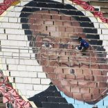 A worker puts final touches on a picture of Zimbabwean President Robert Mugabe at a rally to mark the country's 37th independence anniversary in Harare,  Zimbabwe, April 18, 2017.  REUTERS/Philimon Bulawayo