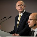 "Jan du Plessis, chairman of Rio Tinto Group, center, pauses during a speech as Samuel ""Sam"" Walsh, outgoing chief executive officer, left, and Tim Paine, joint secretary, right, listen during the company's annual general meeting in Brisbane, Australia, on Thursday, May 5, 2016. Rio Tinto Group, the second-largest mining company, reaffirmed its goal to raise annual iron ore output in Australia to 360 million metric tons amid forecast growth demand in Asia. Photographer: Patrick Hamilton/Bloomberg *** Local Caption *** Jan du Plessis; Sam Walsh; Tim Paine"