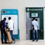 Customers queue to draw money from an ATM outside a branch of South Africa's Nedbank (R) and First National Bank (FNB) at a mall in Midrand outside Johanneburg, South Africa, April 28, 2016.REUTERS/Siphiwe Sibeko