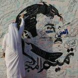 A man writes on a painting depicting Qatar's Emir Sheikh Tamim Bin Hamad Al-Thani in Doha, Qatar, July 2, 2017. REUTERS/Naseem Zeitoon