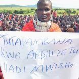 _97406776_a_maasai_woman_holds_a_sign_that_reads_in_swahili_'we_will_fight_for_our_land_until_the_end'