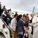 FILE PHOTO: Pope Francis welcomes a group of Syrian refugees after landing at Ciampino airport in Rome following a visit at the Moria refugee camp in the Greek island of Lesbos, April 16, 2016. REUTERS/ Filippo Monteforte