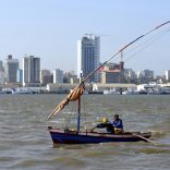 "Traditional fishing boats sail as Mozambique's tuna fleet sits in dock beneath Maputo's skyline, in this picture taken August 15, 2015. Mozambique, one of the world's poorest countries, discovered the reserves off its coast between 2010-2013, offering an opportunity to transform the former Portuguese colony which was ravaged by a 16-year civil war that ended in 1992. Recent signs of reckless government spending and an uptick in political violence have raised concerns that Mozambique could be the latest African country to suffer the resource ""curse,"" in which an influx of petro-dollars suffocates the rest of the economy, encourages corruption and stirs unrest.  Picture taken August 15, 2015.  REUTERS/Grant Lee Neuenburg - RTX1TA2Z"