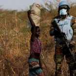 FILE PHOTO: A United Nations Mission in South Sudan (UNMISS) peacekeeping soldier stands guard as children walk by during a patrol close to the town of Bentiu in Rubkona county, northern South Sudan, February 11, 2017. REUTERS/Siegfried Modola/File Photo